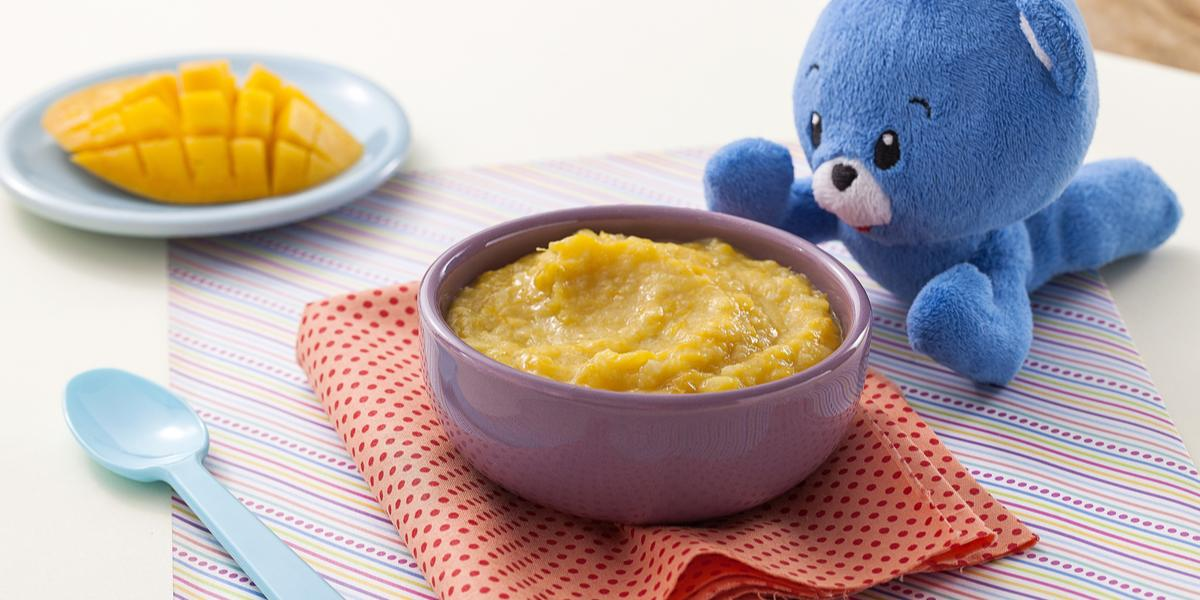Fotografia em tons de amarelo e azul de uma bancada de madeira com um paninho listrado, um potinho roxo com o creminho de manga, ao lado uma colher azul e um ursinho de pelúcia azul. Ao fundo, um pratinho azul com um pedaço de manga cortada.