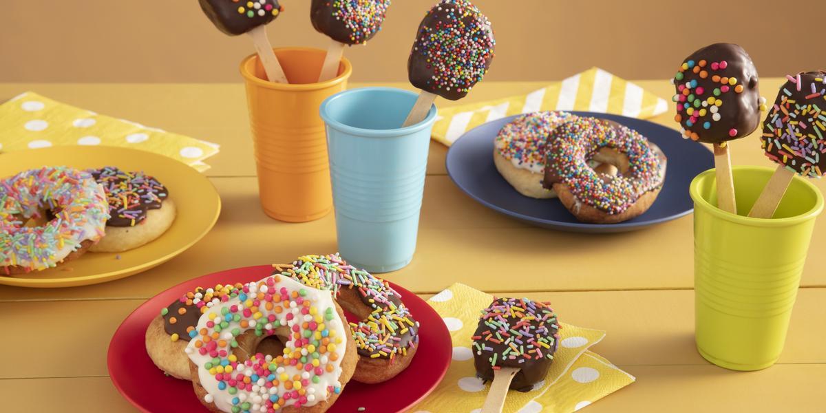 Fotografia em tons de amarelo em uma bancada de madeira amarela com três copos coloridos, azul, laranja e verde com pirulitos de chocolate dentro dele. Ao centro, um prato vermelho com três donuts cobertos com granulados coloridos.