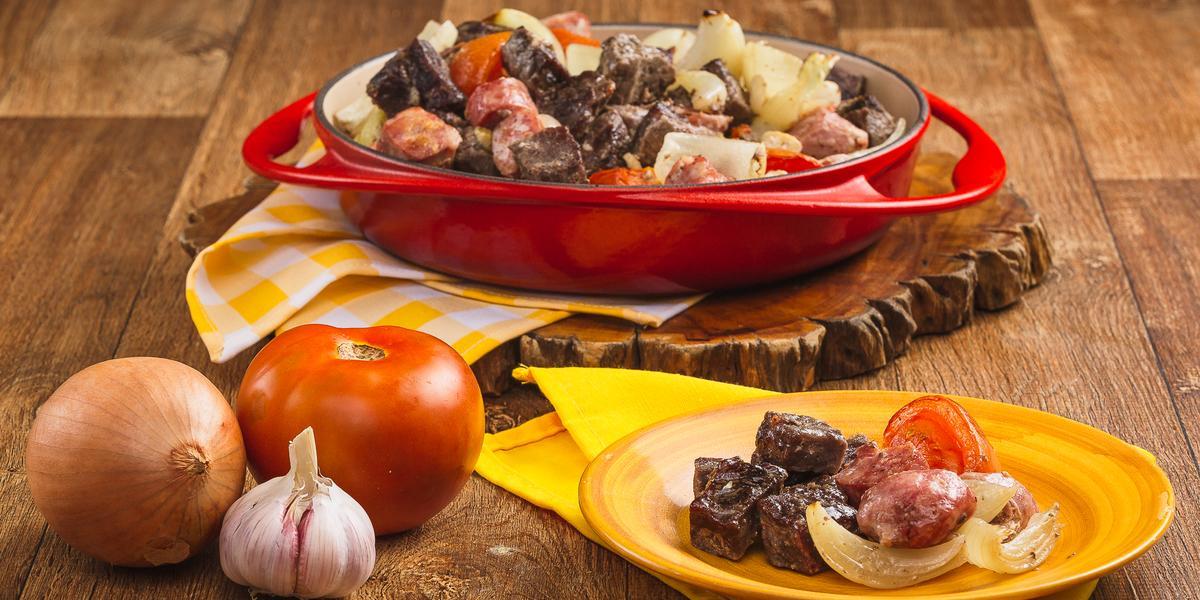Foto de uma bancada de madeira. Nela há uma travessa vermelha com pedaços de carnes, linguiça e legumes, uma cebola, alho e um tomate na bancada e um prato amarelo com mais um pouco da receita de churrasco.