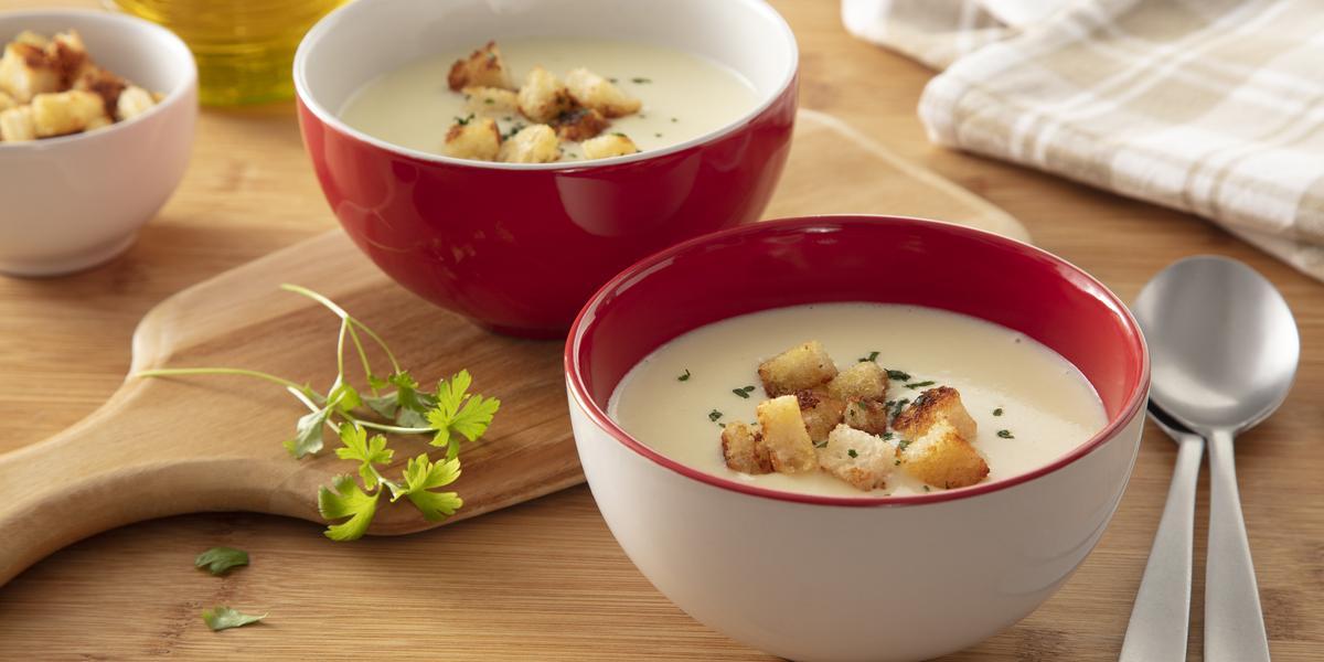 Fotografia em tons de bege e vermelho de uma bancada de madeira, dois potinhos com a sopa dentro e pedacinhos de torrada sobre eles. Ao lado duas colheres pratas.