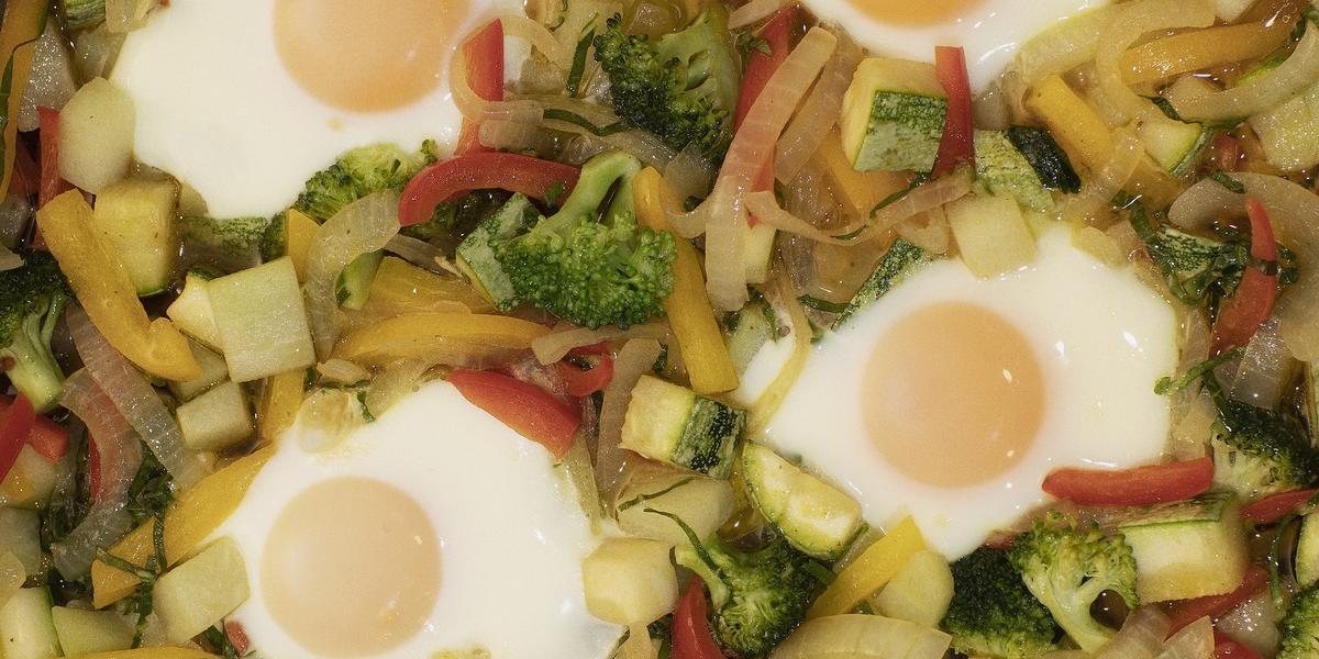 Fotografia em tons coloridos em uma bancada de madeira com uma panela frigideira ao centro, bem aproximada da foto, com ovos fritos e vegetais.