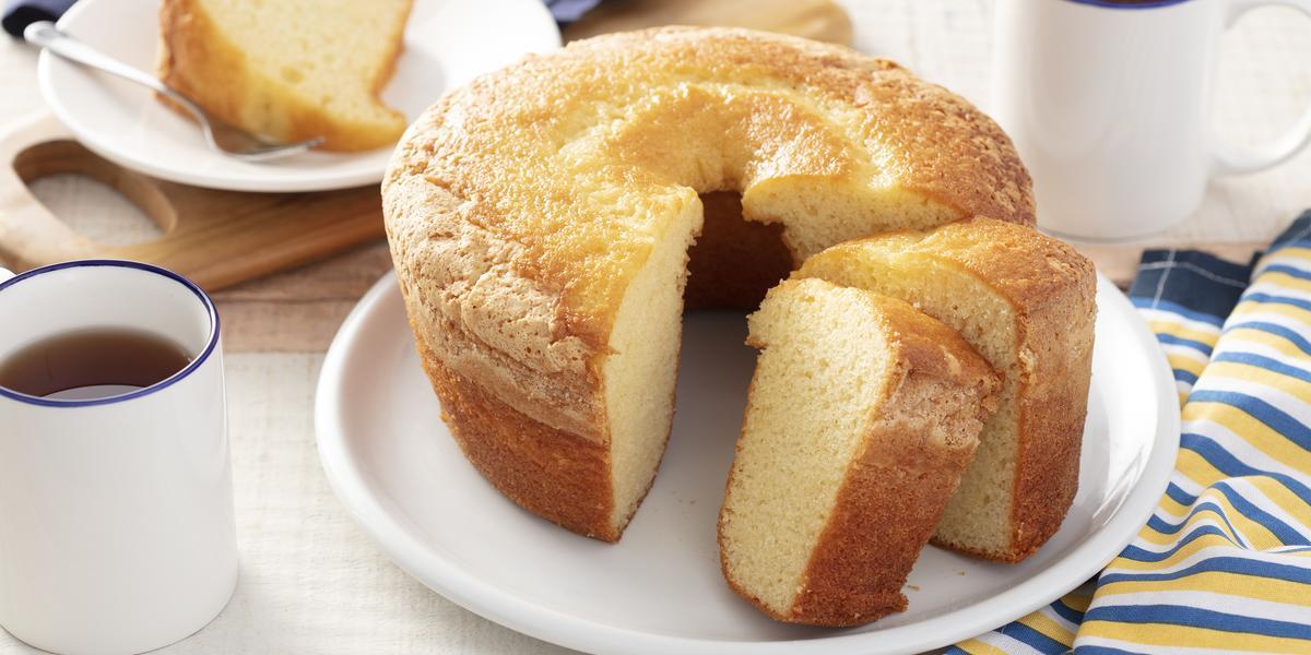 Fotografia em tons de azul e amarelo em uma bancada de madeira com um pano branco com listras azuis e amarelas. Ao centro, um prato branco redondo com o bolo branco em cima dele. Ao lado, xícaras de café e um prato com uma fatia do bolo.