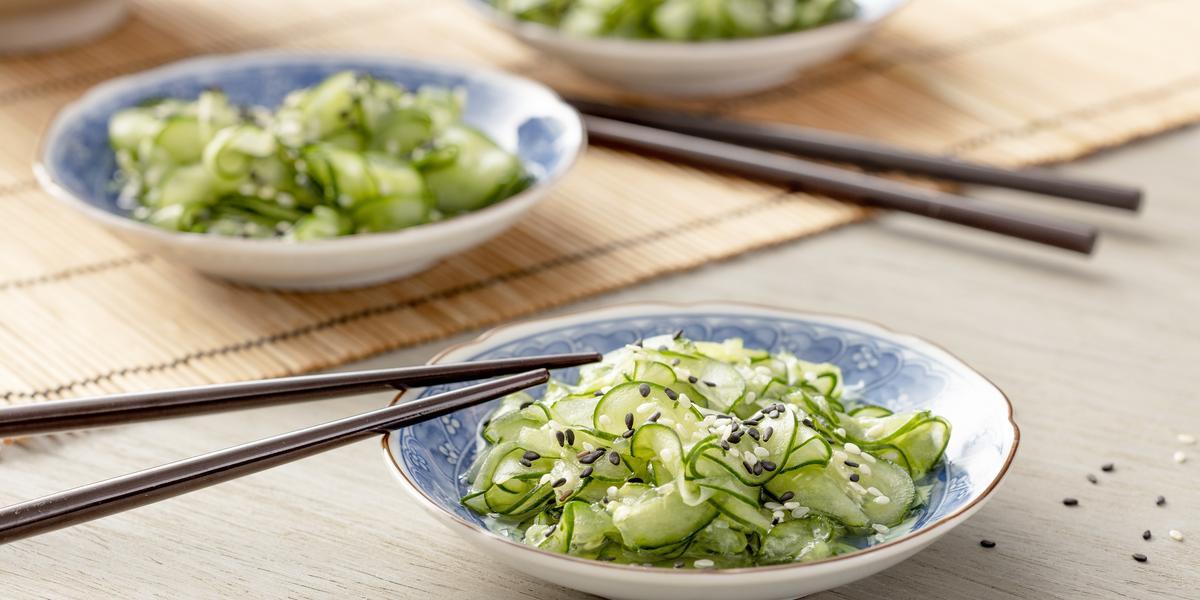 Fotografia em tons de verde em uma bancada de madeira com uma toalha de palha bege. Ao centro, um prato japonês branco com detalhes em azul e a salada de sunomono (pepinos fatiados bem finos) dentro, com um par de hashi apoiado.