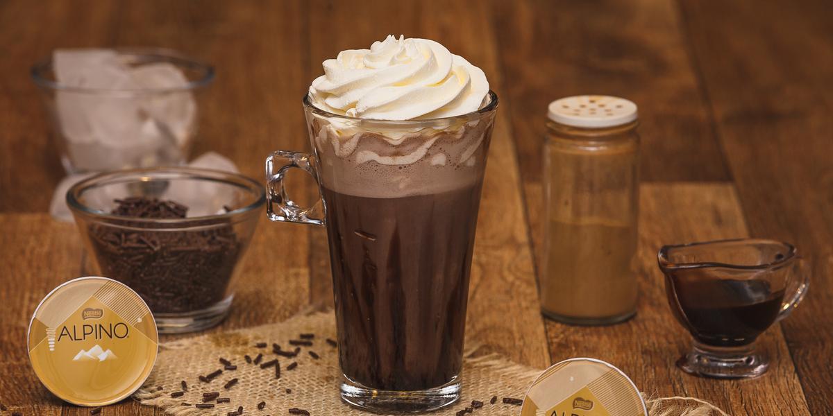 Fotografia em tons de marrom em uma bancada de madeira, com um copo de vidro grande ao centro com a bebida de chocolate Alpino. Ao fundo, um copo com gelo, um potinho com chocolate granulado, e um potinho com canela.