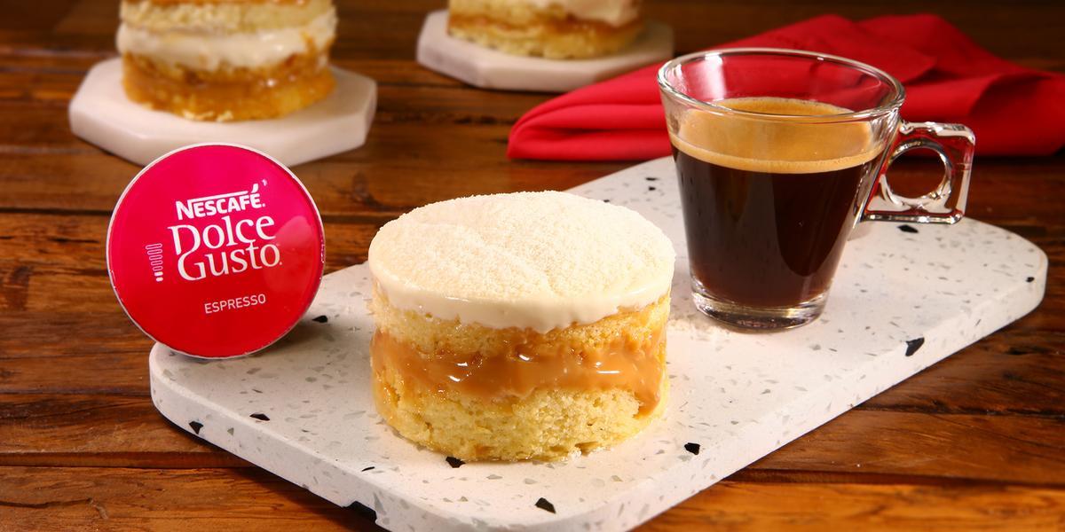 Fotografia em tons de vermelho em uma bancada de madeira escura, uma tábua de pedra branca com uma sobremesa de mini bolinho recheado com leite em pó e doce de leite. Ao lado, uma cápsula de Nescafé Dolce Gusto e uma xícara com o café pronto.