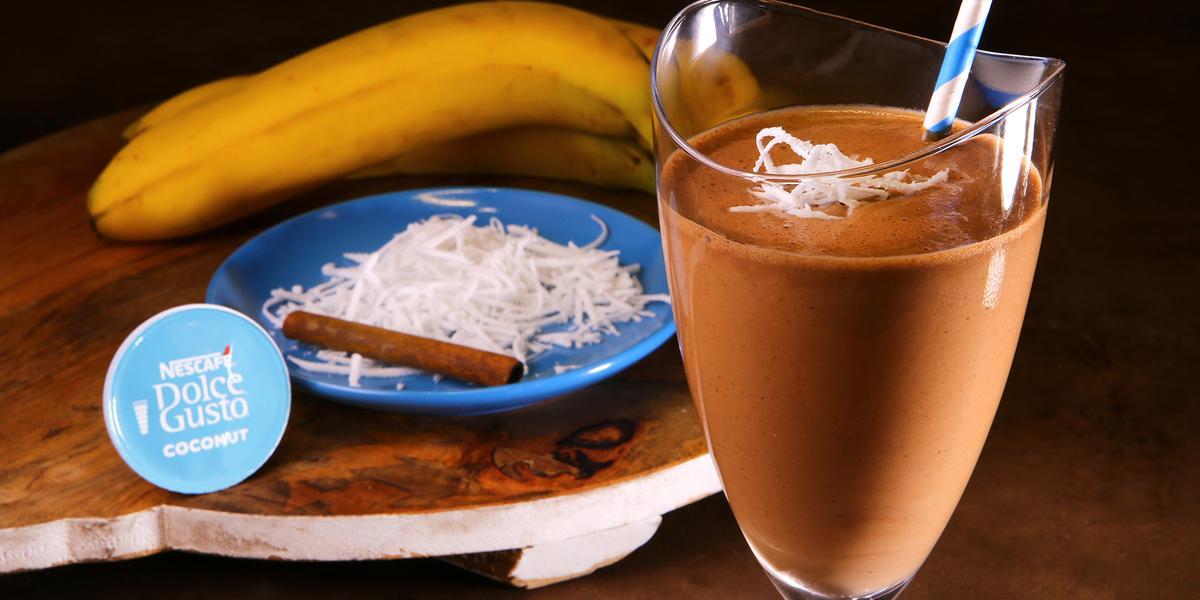 Fotografia em tons de azul em uma bancada de madeira, uma tábua de madeira com um copo de vidro alto e a bebida de chocolate com coco e banana dentro dele. Ao fundo, um prato azul com raspas de coco, uma canela em pau e uma banana.