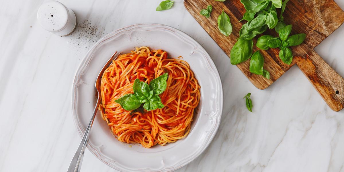 fotografia em tons de branco e vermelho de uma bancada branca vista de cima. Ao centro um prato branco com macarrão espaguete e molho de tomate, e ao lado uma tábua com folhas.