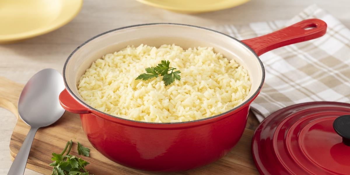Fotografia em tons de vermelho de uma bancada branca, ao centro uma panela vermelha por fora e banca por dentro com arroz levemente amarelado. No topo, uma folha de salsinha decorando.