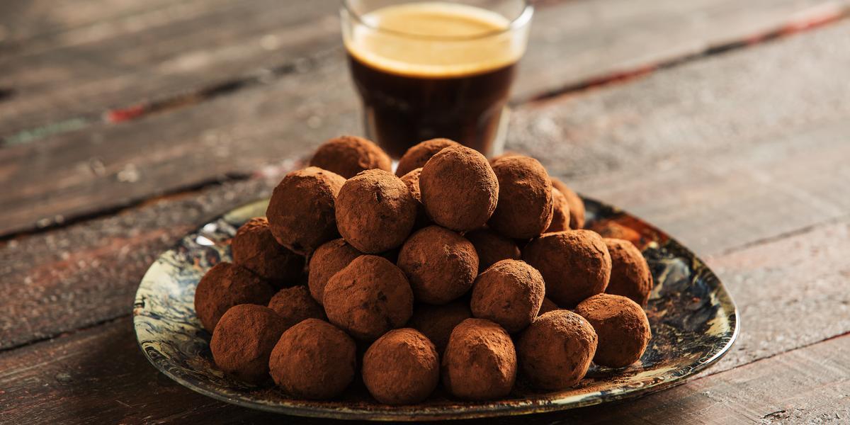 fotografia em tons de marrom e preto de uma bancada marrom vista de frente, contém um prato redondo com trufas com chocolate, e ao fundo um copo com café.