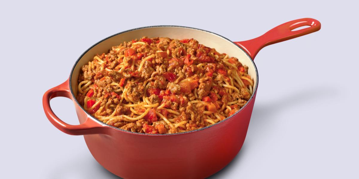 Fotografia em tons de vermelho e marrom de uma panela vermelha com macarrão espaguete ao molho bolonhesa dentro.