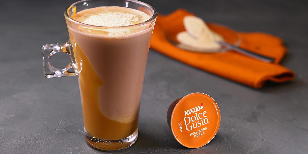Fotografia em tons de laranja em uma bancada de madeira cinza escura, um paninho laranja e uma xícara de vidro alta com o café de mochaccino canela com doce de leite e achocolatado Galak.