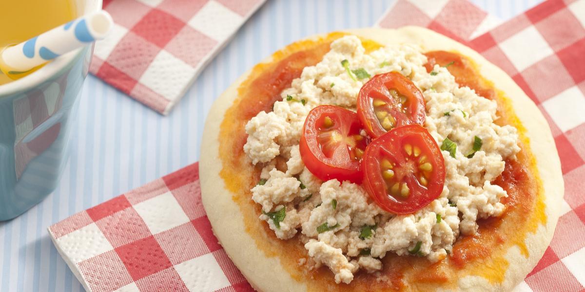 Fotografia em tons de vermelho em uma bancada cinza com guardanapos vermelhos em xadrez e uma mini pizza de legumes e outra mini pizza de tofu apoiadas sobre eles. Ao lado, um copo laranja com suco de laranja e um canudo branco com bolinha azul.
