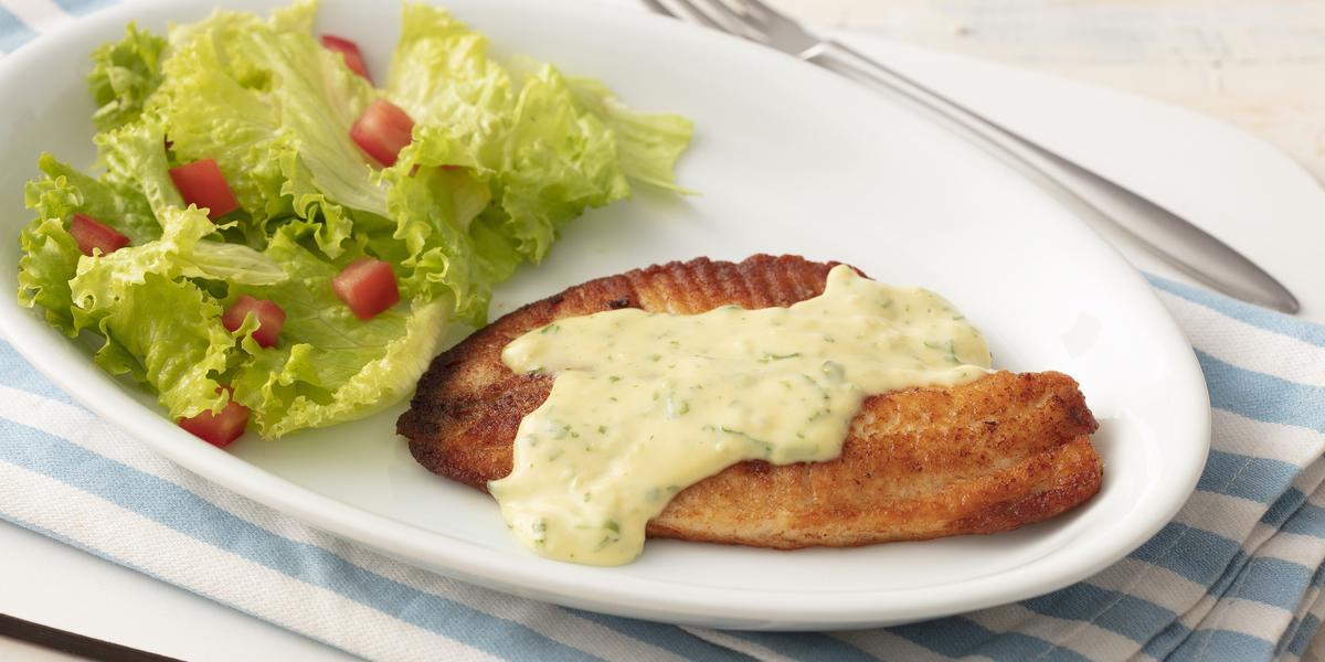 Fotografia em tons de azul em uma bancada de madeira clara com um pano listrado azul claro e um prato oval branco com o filé de pescada com molho de limão e mostrada e salada de alface com tomates.