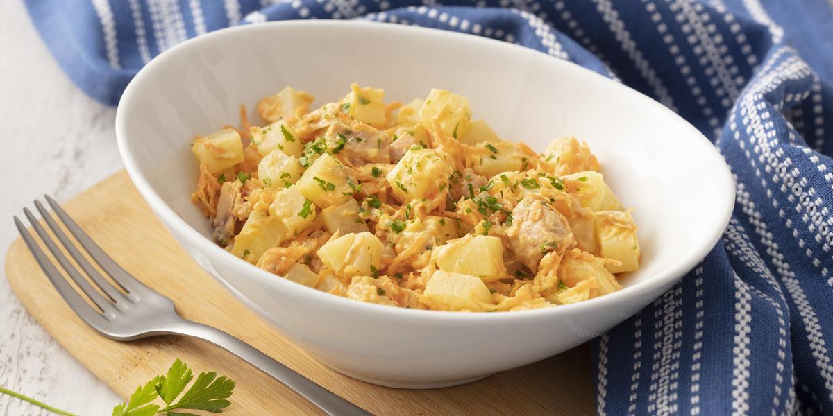 Fotografia em tons de azul em uma bancada de madeira com um pano listrado azul ao lado. No centro, um prato fundo branco com a salada de batata, atum, cebola e salsinha.
