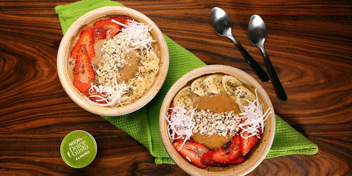 Fotografia em tons de verde em uma bancada de madeira escura, um pano verde, dois bowls bege com morango, banana e lascas de coco e duas colheres ao lado.
