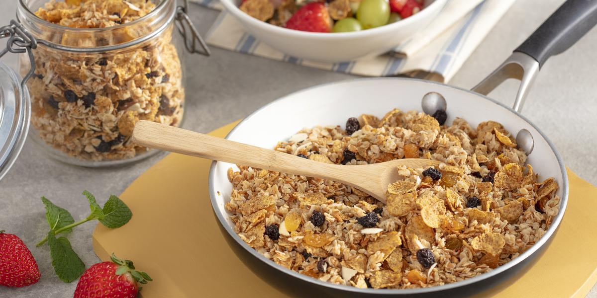 Fotografia em tons de amarelo em uma bancada de madeira com uma tábua de madeira, uma frigideira grande dentro com a granola com uvas-passas, cereal matinal dentro. Ao lado, um potinho com a granola e ao lado um outro potinho branco com frutas.