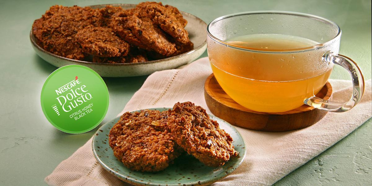 Fotografia em tons de verde em uma bancada de cimento queimado, um pano rosinha com um prato pequeno e os biscoitos de ameixa com aveia. Ao lado, uma xícara de vidro com o chá cítrico e a cápsula verde da Dolce Gusto do Chá Cítrico.