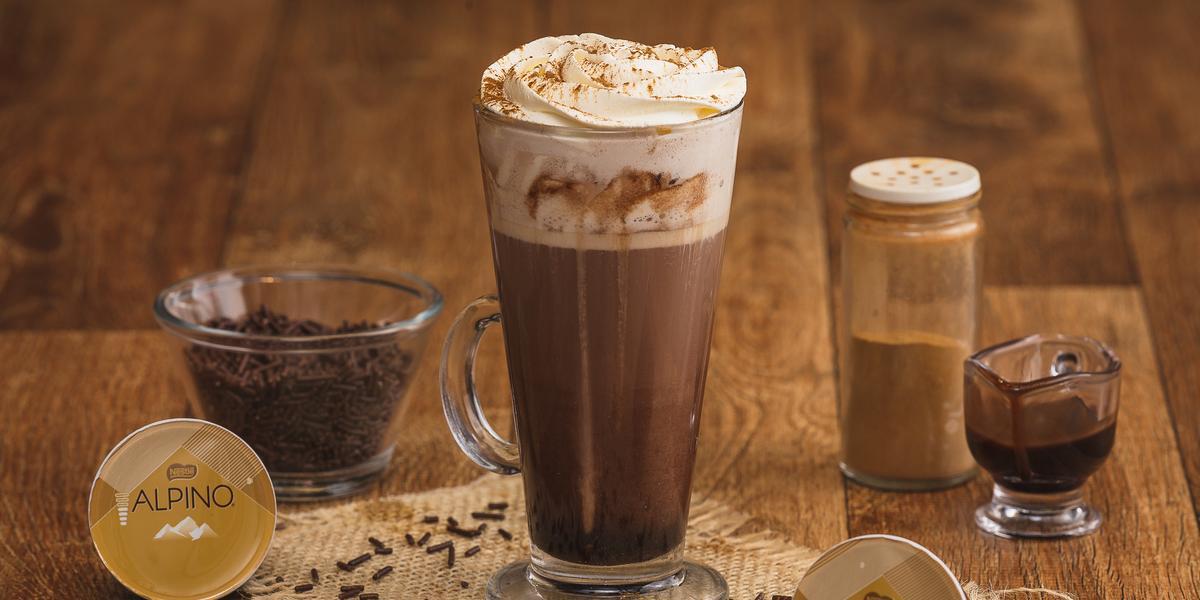 Fotografia em tons de marrom em uma bancada de madeira com um copo grande de vidro com a bebida de Alpino, chocolate quente. Ao fundo, cápsulas de alpino da Dolce Gusto, um vidrinho de canela, um copinho com raspas de chocolate.