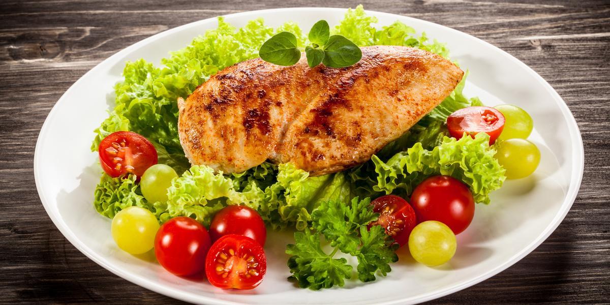 fotografia em tons de branco, verde, cinza e amarelo de uma bancada cinza vista de cima, ao centro um prato redondo e branco com folhas de alfaces, fatias de tomates-cereja e um filé de frango assado por cima das folhas de alface.
