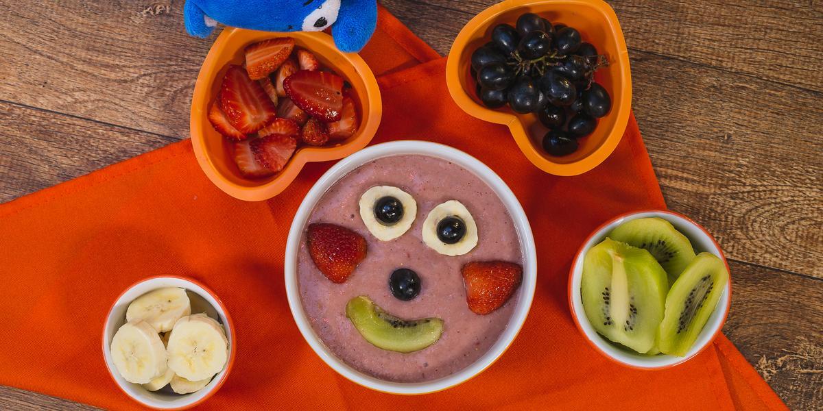 Fotografia em tons de laranja em uma bancada de madeira escura, um pano laranja, um recipiente redondo com o smoothie de morango, banana e kiwi dentro dele e frutinhas formando um rostinho feliz. Ao lado, potinhos com as frutas e o ursinho azul de pelúcia
