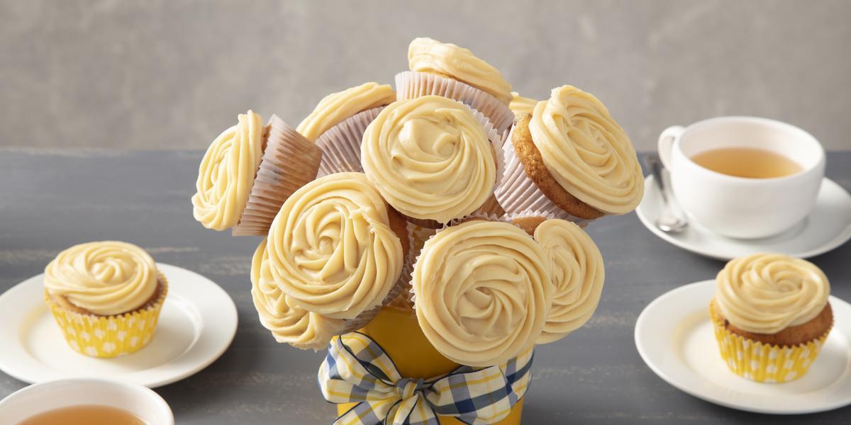 Fotografia em tons de amarelo em uma bancada cinza com um vaso de buquê de cupcake ao centro com um laço xadrez em amarelo e azul. Ao lado, xícaras brancas com chá e pratos brancos com um cupcake em cada um.