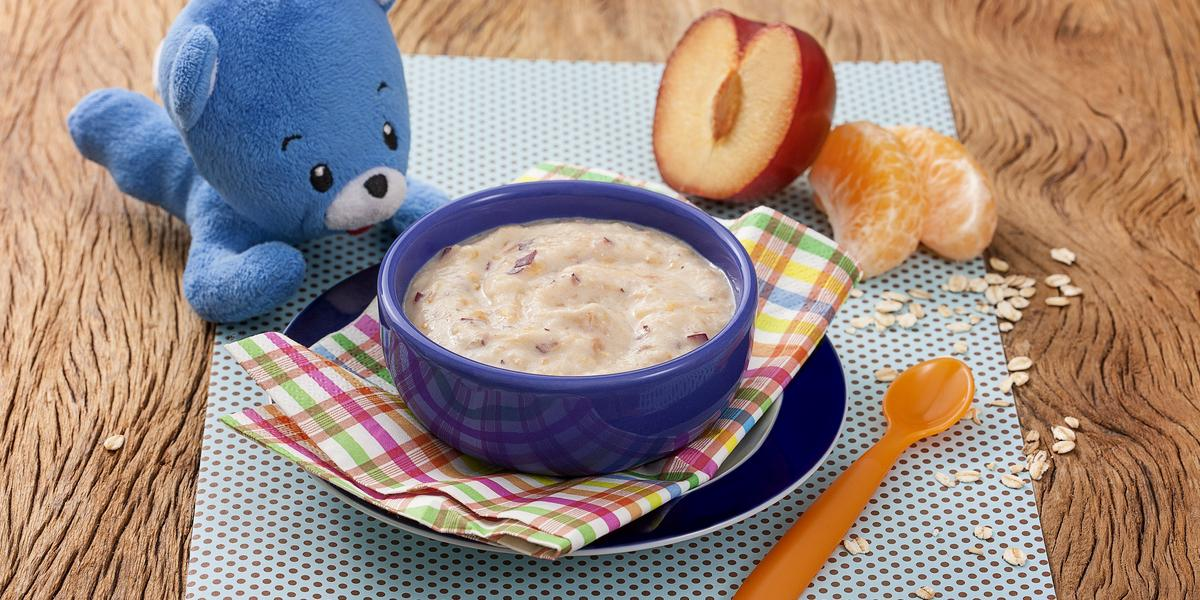 Fotografia em tons de azul em uma bancada de madeira um paninho azul com bolinhas roxas e um potinho roxo com o purezinho de ameixa com mexerica. Ao lado, um ursinho de pelúcia azul, um pedaço de ameixa e dois gomos de mexerica.