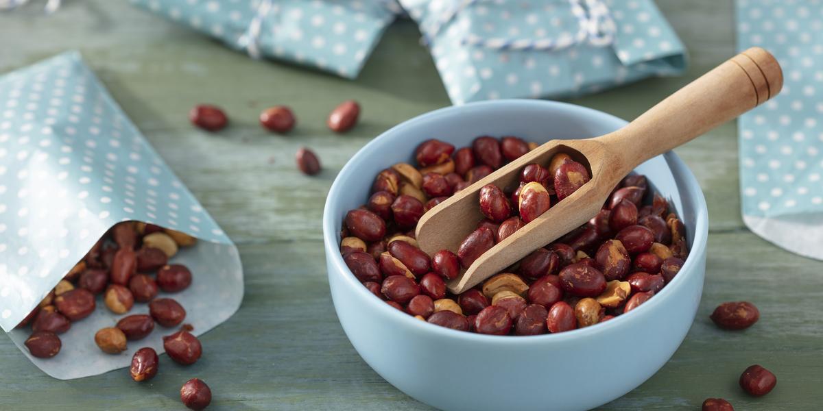 Fotografia em tons de azul em uma bancada de madeira azul, um pote azul redondo fundo com os amendoins torrados e um pegador de madeira. Ao lado, saquinhos de papel azul com bolinhas brancas com amendoins dentro deles.