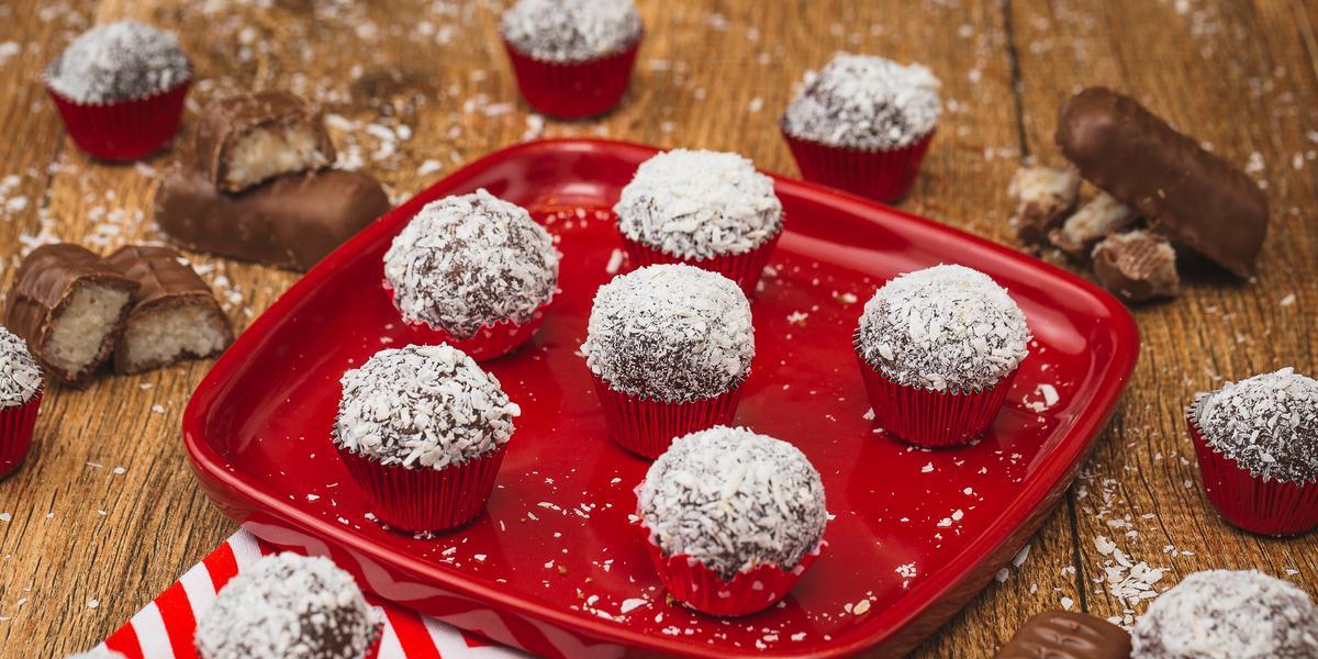 Imagem de uma prato vermelho com algumas unidades de Brigadeiro marrom passado em flocos de coco. A bancada está decorada com pedaços de bombons, um tecido vermelho e branco e mais brigadeiros.