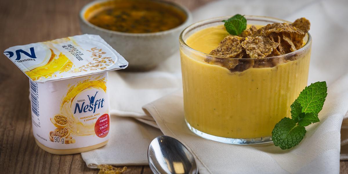 Fotografia em tons de amarelo em uma bancada de madeira, um paninho bege, um potinho com um creme de iogurte de maracujá com gengibre. Ao lado, um potinho de maracujá e uma colher.