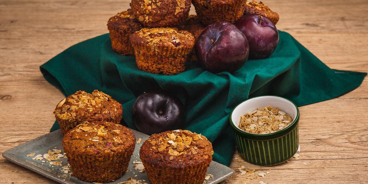 Fotografia em tons de verde em uma bancada de madeira clara, um pano verde, um recipiente retangular com os muffins de ameixa e cereais em cima. Ao lado, um potinho com cereais. Ao fundo, um suporte com o pano verde e mais muffins e ameixas.