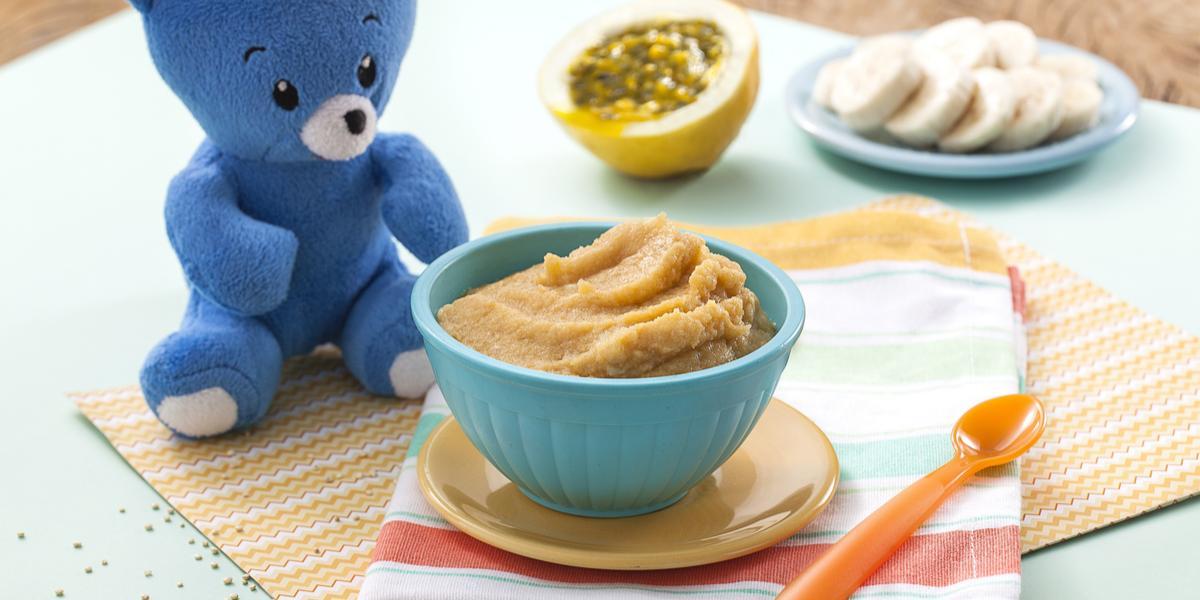 Fotografia em tons de azul em uma bancada de madeira com paninho listrado em azul e vermelho e um potinho azul com a delicinha de maracujá sobre um pratinho laranja, ao lado um ursinho de pelúcia azul. Ao fundo, um pedaço de maracujá e fatias de banana.