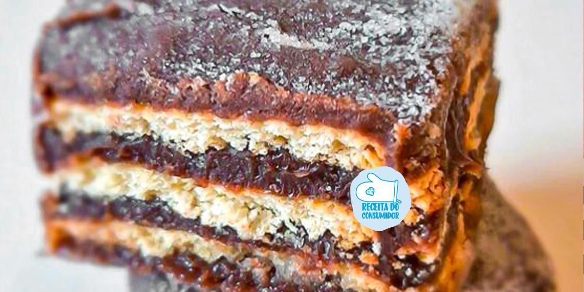 Imagem bem aproximada de uma fatia de Palha Italiana com camadas intercaladas de brigadeiro em tom marrom escuro e biscoitos em tom marrom claro