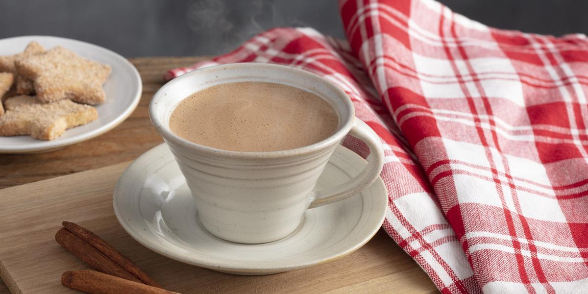Fotografia em tons de vermelho e marrom de uma bancada, ao centro uma xícara com chocolate quente saindo fumaça e um pires abaixo. Ao lado pedaços de canela, biscoitinhos e uma pano xadrez vermelho e branco.