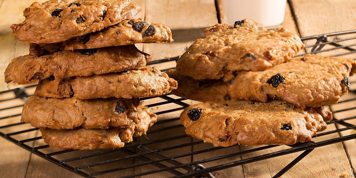Fotografia em tons de marrom em uma bancada de madeira com um suporte de grades preta com vários cookies com nuts e berries apoiados sobre ele. Ao fundo, um copo de vidro com a Bebida Vegetal de Aveia.