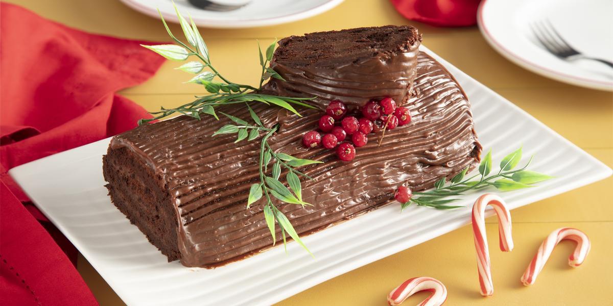 Fotografia em tons de vermelho em uma bancada de madeira amarela, um pano vermelho ao lado e ao centro, um recipiente retangular branco com o rocambole de chocolate em cima com decoração natalina.