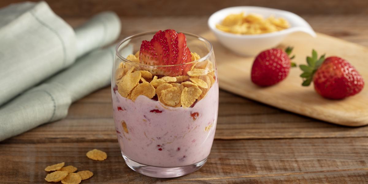 Fotografia em tons de marrom e rosa em uma bancada de madeira com um copo de vidro ao centro, com iogurte, cereais e morangos. Ao fundo, uma tábua de madeira com dois morangos e um potinho branco com cereais.
