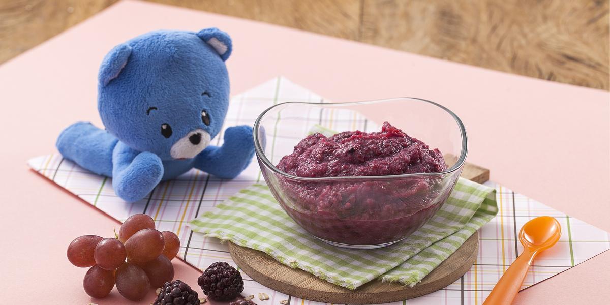 Fotografia de uma bancada de madeira com um paninho rosa, sobre ele um potinho transparente com uma papinha roxa, à frente uvas e amoras e ao lado um ursinho de pelúcia azul.