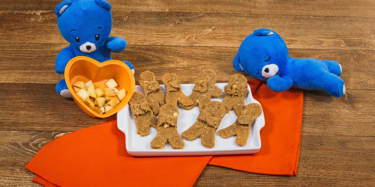 Fotografia em tons de laranja em uma bancada de madeira escura, um pano laranja, um recipiente branco retangular com vários biscoitinhos em formato de bonequinho abraçados com maçã. Ao lado, ursinhos de pelúcia azul.