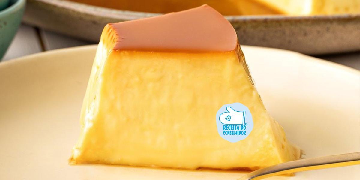 Imagem aproximada de uma fatia de Pudim em tons amarelo e marrom, em um prato claro e com um talher próximo