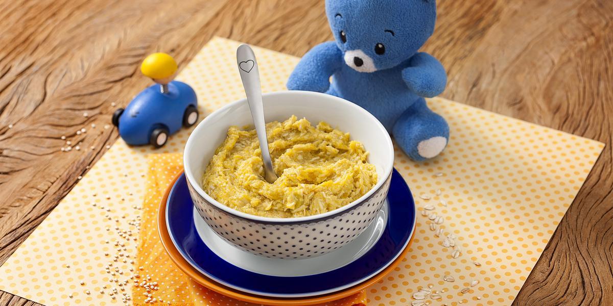 Fotografia em tons de laranja em uma bancada de madeira com um paninho amarelo de bolinha no centro e um potinho branco com bolinhas azuis com a sopinha de frango com abóbora. Ao lado, um ursinho de pelúcia azul e um carrinho azul de brinquedo.