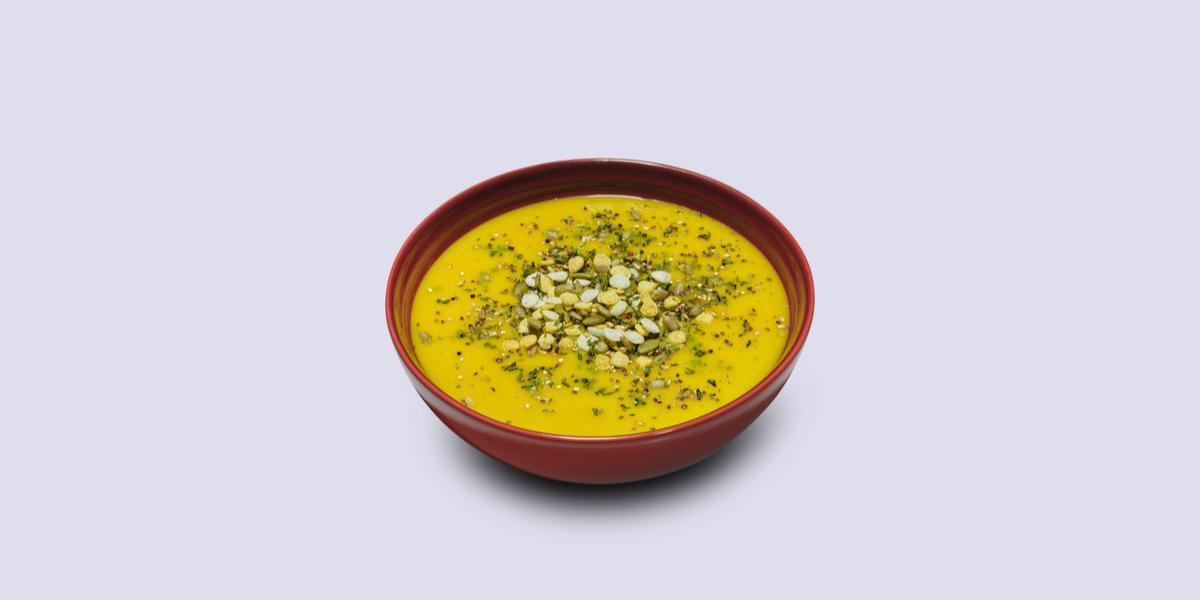 Fotografia em tons de amarelo em um fundo branco com um prato fundo vermelho e o caldo de abóbora e carne seca com Maggi dentro.