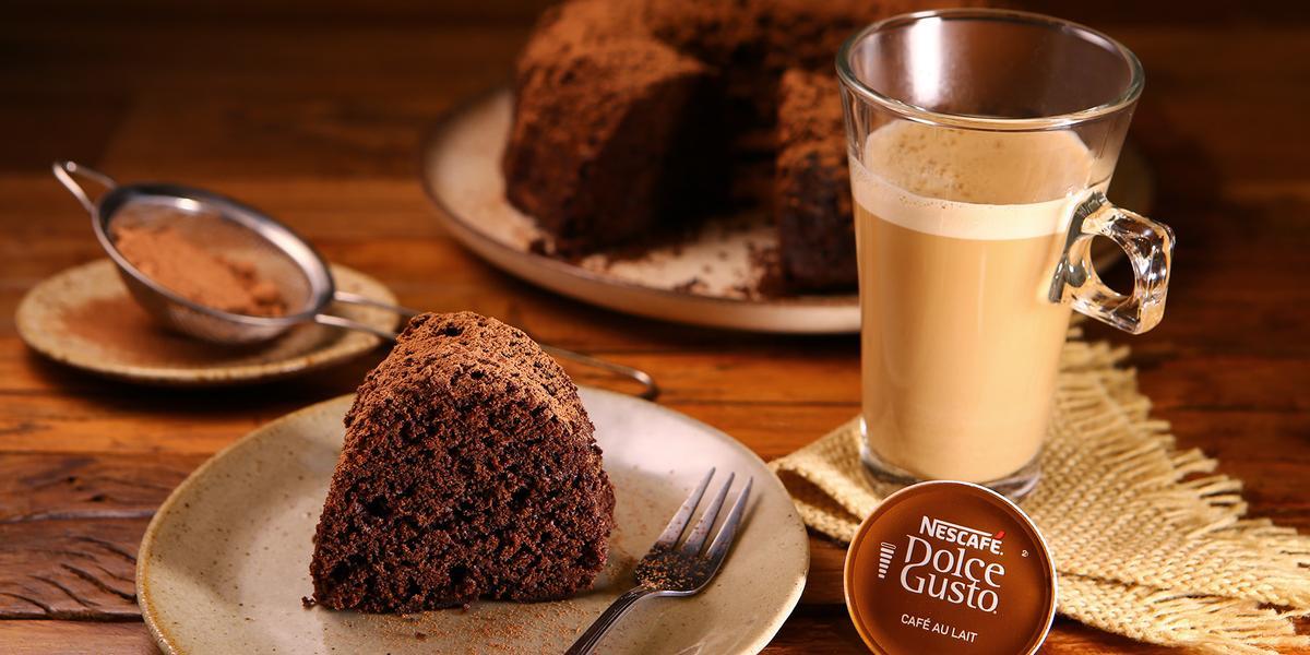 Fotografia em tons de marrom em uma bancada de madeira clara, um guardanapo de pano bege de palha, uma xícara em cima com o Café ao Leite Dolce Gusto. Ao centro, um prato redondo com um pedaço do bolo de chocolate em cima dele. Ao fundo, o bolo inteiro.