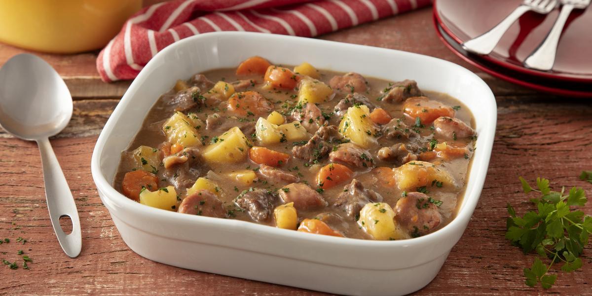 Fotografia em tons de marrom de uma bancada de madeira, ao centro uma travessa com o cozido de carne, linguiça, batata e cenoura com bastante molho.