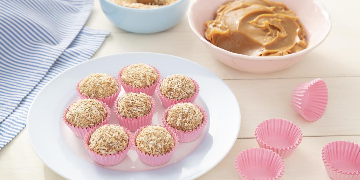 Fotografia em tons de rosa e azul de uma bancada branca, ao centro um prato com docinhos em forminhas rosa, ao fundo um pote com doce de leite e um pote com coco ralado, ao lado forminhas para docinho rosa vazias.